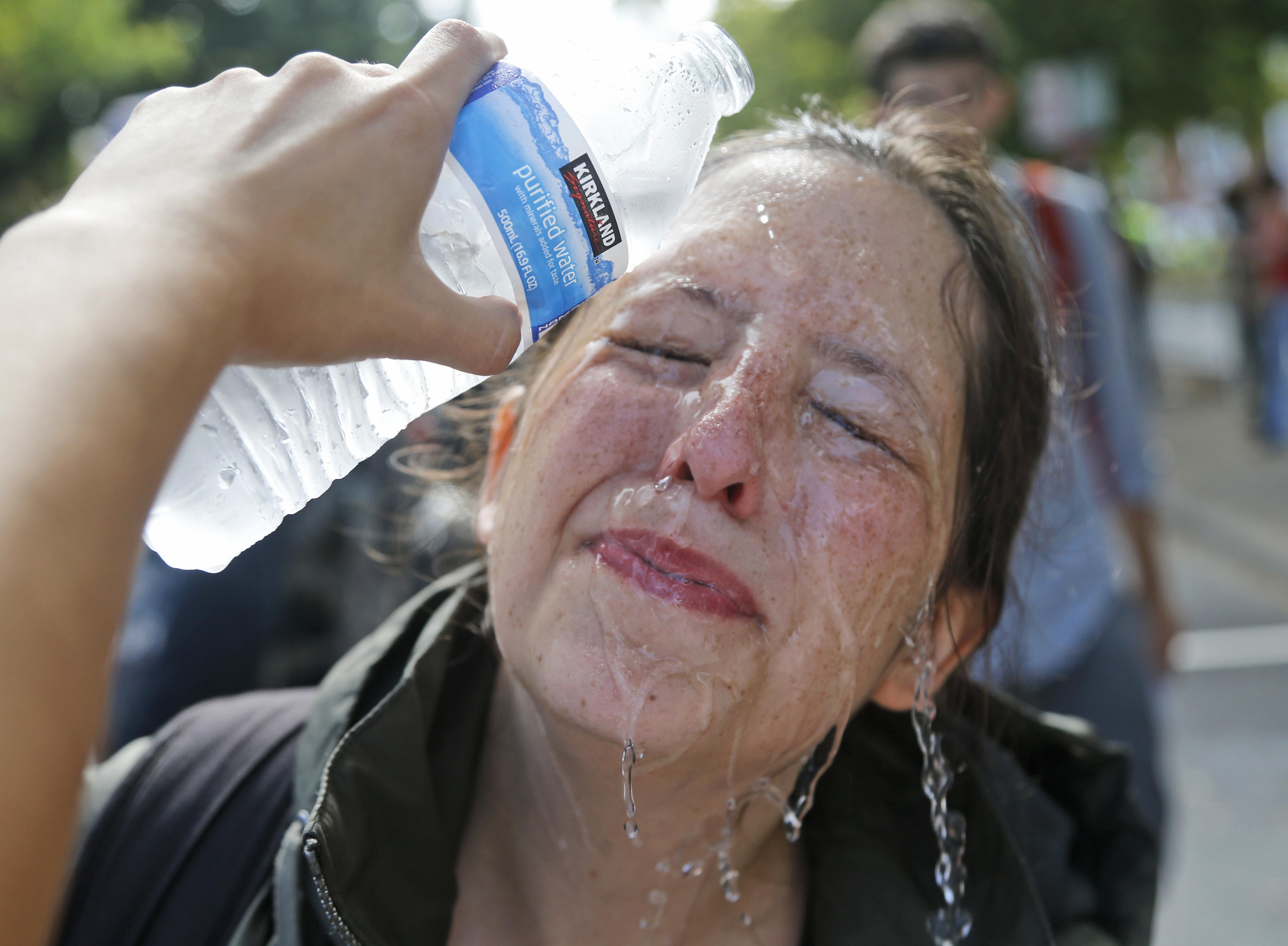 擁護白人至上主義的民眾與反對人士爆發流血衝突,圖為一名反對人士遭胡椒噴劑攻擊到雙眼後,潑水處理傷口。(美聯社)