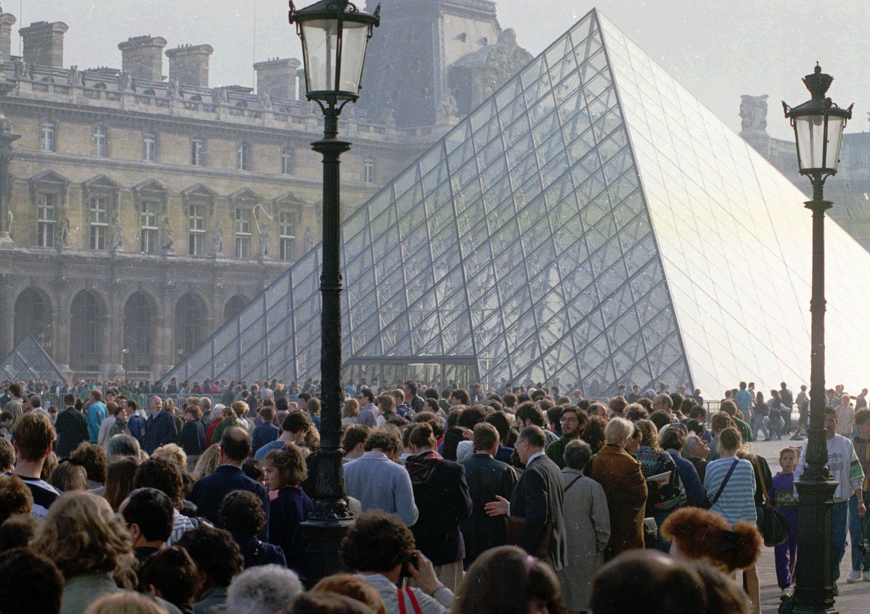 1989年3月30日,上百名民眾聚集在羅浮宮前觀看玻璃金字塔。 法總統於同一年委託華裔名建築師貝聿銘設計了一座玻璃金字塔,作為羅浮宮入口處。 (美聯社)
