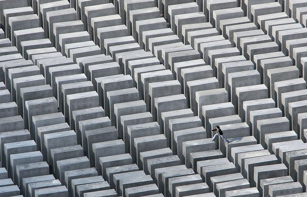 2005年一個參觀民眾在德國柏林的猶太屠殺紀念碑,從一個墓碑跳到另一個的景象。(Getty Images)
