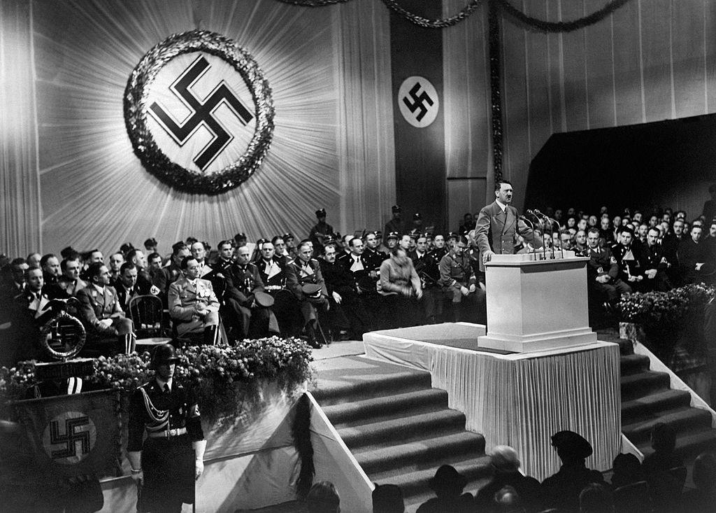 1939年希特勒在納粹黨集會時演講,照片中的大標誌即為納粹黨黨徽。(Getty Images)
