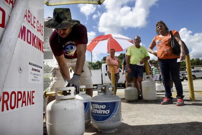 液化瓦斯也引起搶購,圖為佛州戴維一處加油站,民眾拎著空罐等候灌裝。(美聯社)