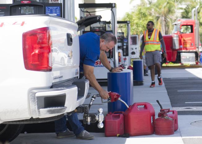 佛州邁阿密居民搶購汽油,除了加滿油箱,還帶了大大小小的後備油桶。(美聯社)