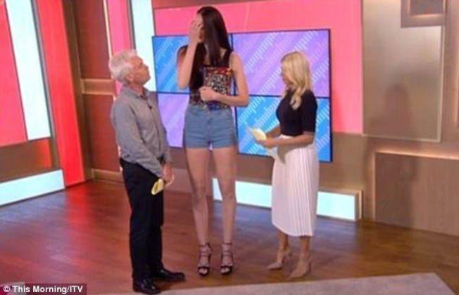 一沒了梯子,男女主持在艾卡塔琳娜身旁,有如哈比人。圖/摘自ITV