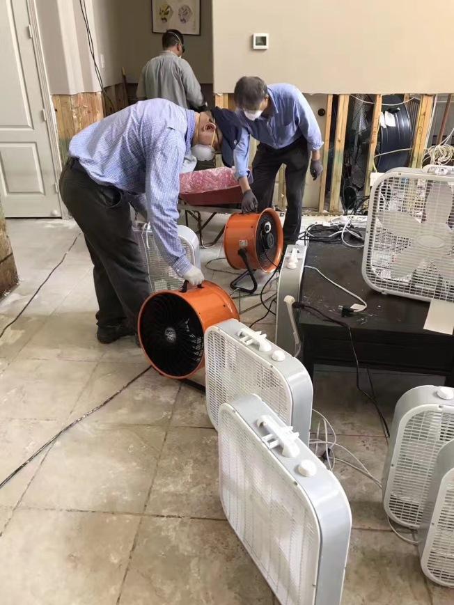 義工安裝風扇,吹乾浸水物品。(讀者提供)