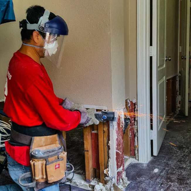 義工協助災民拆除泡水牆壁。(華裔聯盟提供)