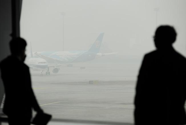 圖為北京首都國際機場,候機乘客透過玻璃觀看籠罩在霧霾中的飛機。(中新社)