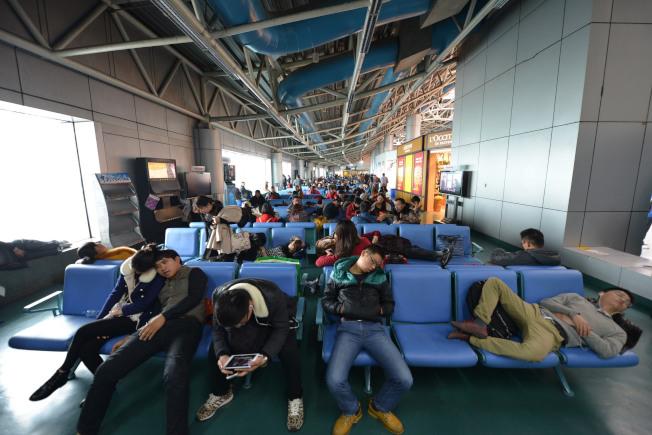 首都機場近日完成使用平視顯示器在跑道視程150米低能見度下的驗證試飛,未來有望大幅提升準點率。圖為旅客滯留在機場候機區。(新華社)