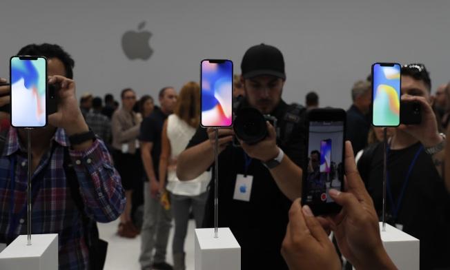 蘋果公布三款新的iPhone,參加發布會的群眾排隊體驗新功能。(路透)