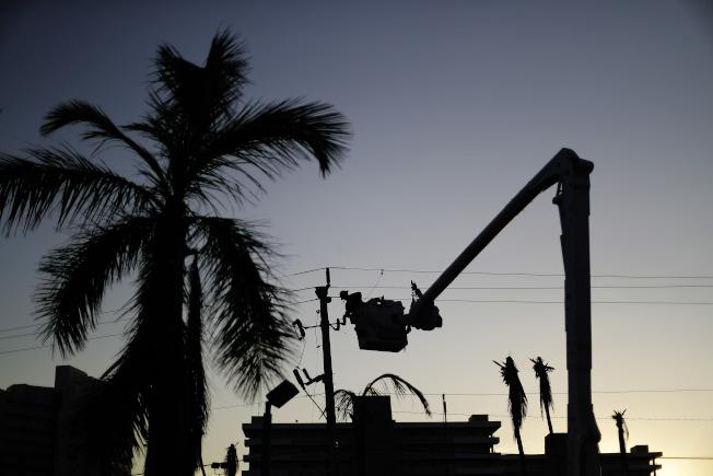 颶風厄瑪造成佛州大規模停電,圖為工作人員在佛州馬可島搶修供電。(美聯社)