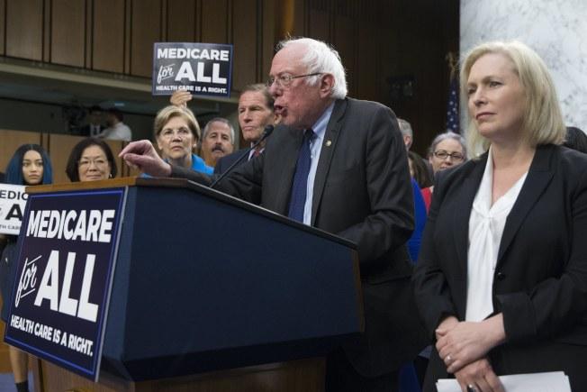 佛蒙特州國會參議員桑德斯(前右二)提出單一付款人的全民健保案,獲民主黨自由派參議員支持。(歐新社)