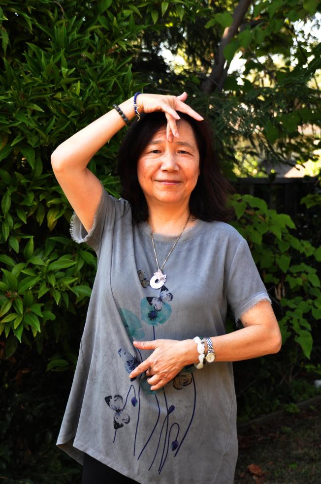 陳玲表示,將兩手中指分別放在肚臍、眉心,調整能量流,就能改善部分身體不適的症狀。(記者林亞歆/攝影)