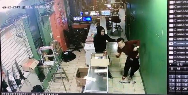 其中一名非洲裔歹徒(左)拖著員工方先生(右)到收銀台。(截自監視器畫面)