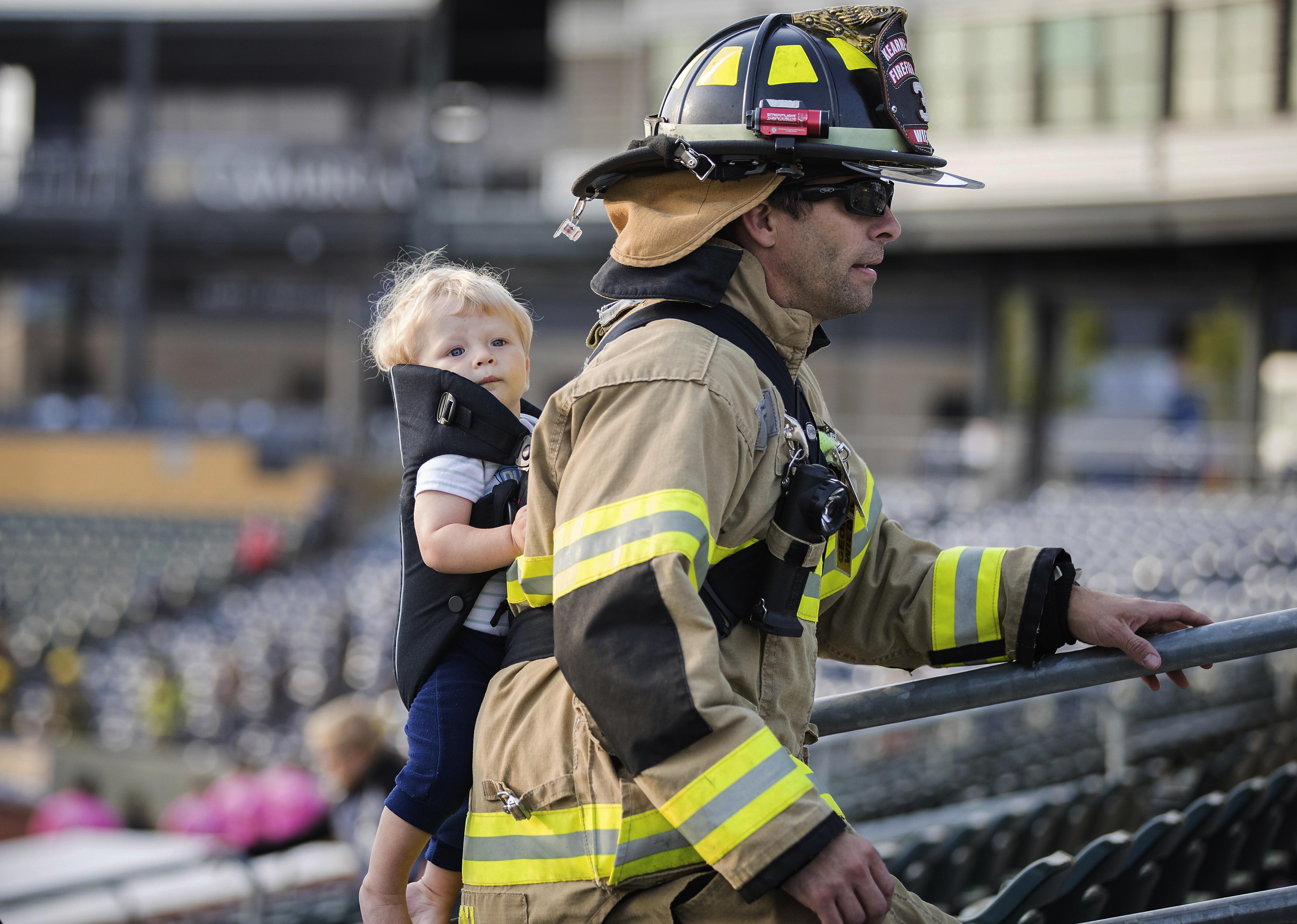 今年9月9日當時參與救難的消防員George Wiedel 背著年幼的兒子重返災難現場爬樓梯,緬懷自己的弟兄。美聯社