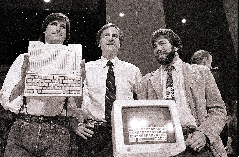 1984年4月24日,蘋果公司董事長賈伯斯(左)與執行長John Sculley(中)、共同創辦人沃茲尼亞克(Stephen Wozniak)在舊金山展示第二代蘋果電腦Apple IIc。(美聯社)