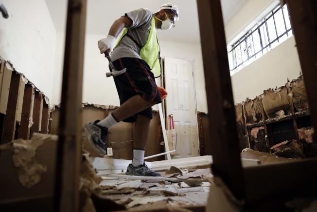 房屋進水後,需要將被水浸泡的牆壁拆除。(路透)