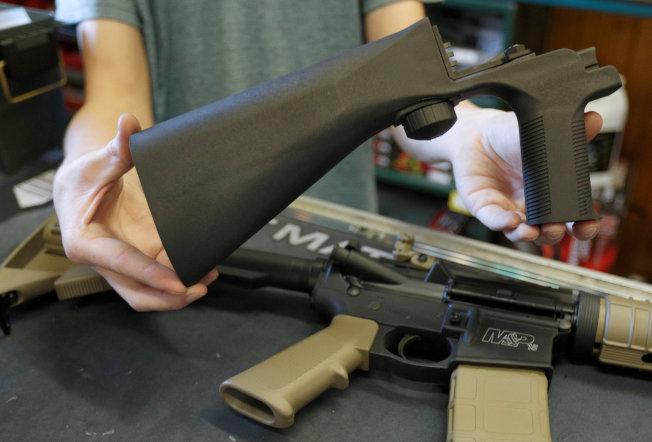 一把半自動步槍若裝上「撞火槍托」,可以增加射速,圖為槍店人員展示撞火槍托。(路透)