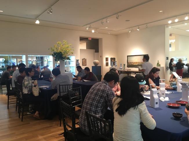 紐約亞洲藝術周,來自全球多個國家和地區的收藏家、藝術愛好者及骨董經紀人前來「趕集」,以華人臉孔為多。圖為蘇富比現場買家在開拍前紛紛鑑寶,人氣旺盛。(記者曾慧燕/攝影)