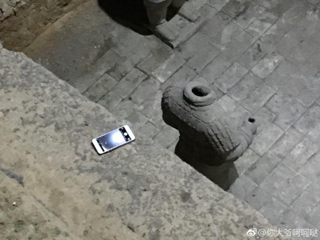 成都一名男子參觀兵馬俑土坑時,一時手滑,手機竟掉入土坑內。(取材自微博)