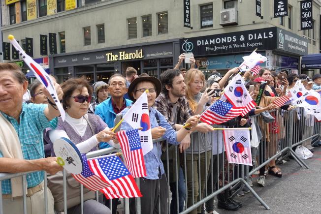 街邊韓裔民眾揮舞兩國國旗慶祝。(記者金春香/攝影)