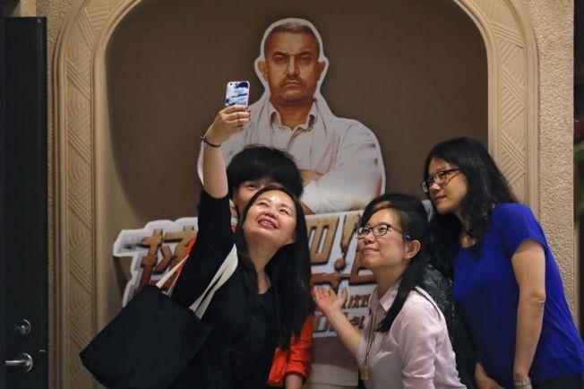 北京女子與阿米爾·罕的人型立牌合照。 (美聯社)
