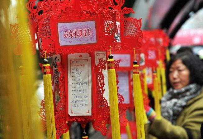 上海人民公園在情人節懸挂起百餘盞「心緣求偶花燈」,長廊上貼著尋覓姻緣者的基本信息、擇偶要求等。 (新華社)