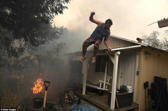 山火燒進住宅區,一名居民在濃煙密布時躍身逃脫大火。(Getty Images)