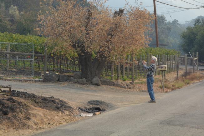 居民普爾的先生約翰的房子在山火中燒毀,他在現場給房子拍照留念。(記者劉先進/攝影)