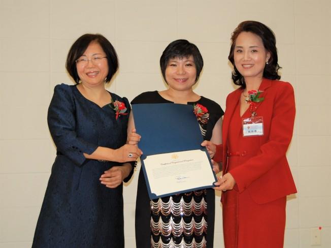 國會眾議員皮特‧奧爾森的華裔代表張晶晶(中)向騰龍教育學院俞曉春校長(右)、王濤頒發議員賀函。(記者賈忠/攝影)