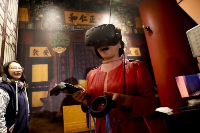 圖為遊客運用VR技術參觀養心殿。(中新社)