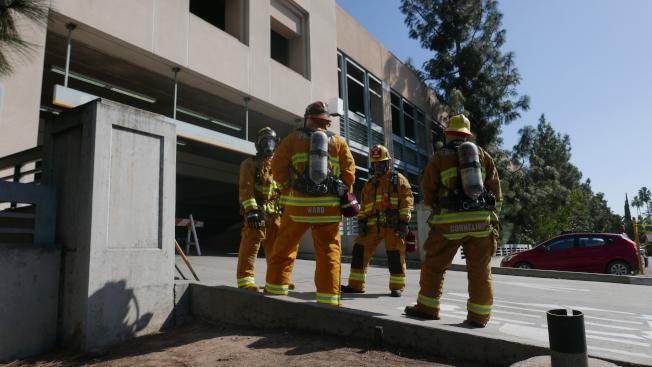 一些消防人員全副武裝在停車樓下待命。(記者李雪/攝影)