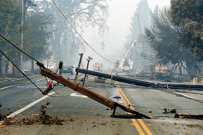 電線桿和電線被吹倒,可能是這次北灣大火的原因。(美聯社)