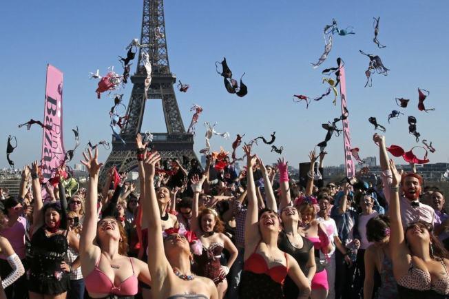 眾多女性在巴黎鐵塔前將內衣拋向天空,響應乳癌相關活動。(路透)