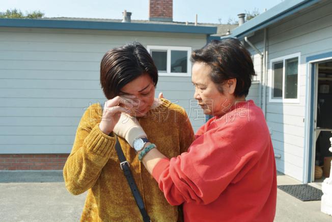紅木區華人協會會長王潘瑞貽(右)在安慰火災中失去家園的黃豔瓊(左)。(記者劉先進/攝影)