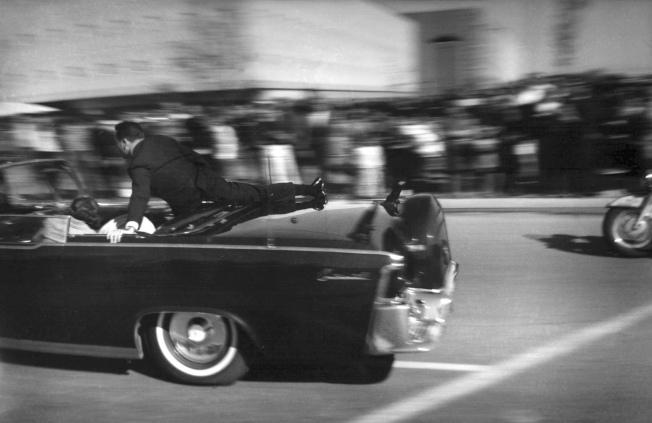 甘迺迪總統被刺後,敞篷車立即加速趕往醫院,特勤人員俯在車上保護總統和第一夫人。(美聯社)