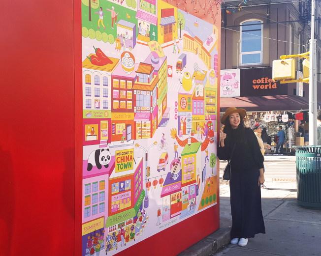 胡丁玎在曼哈頓華埠與自己的作品「華埠歡迎你」合影。(胡丁玎提供)
