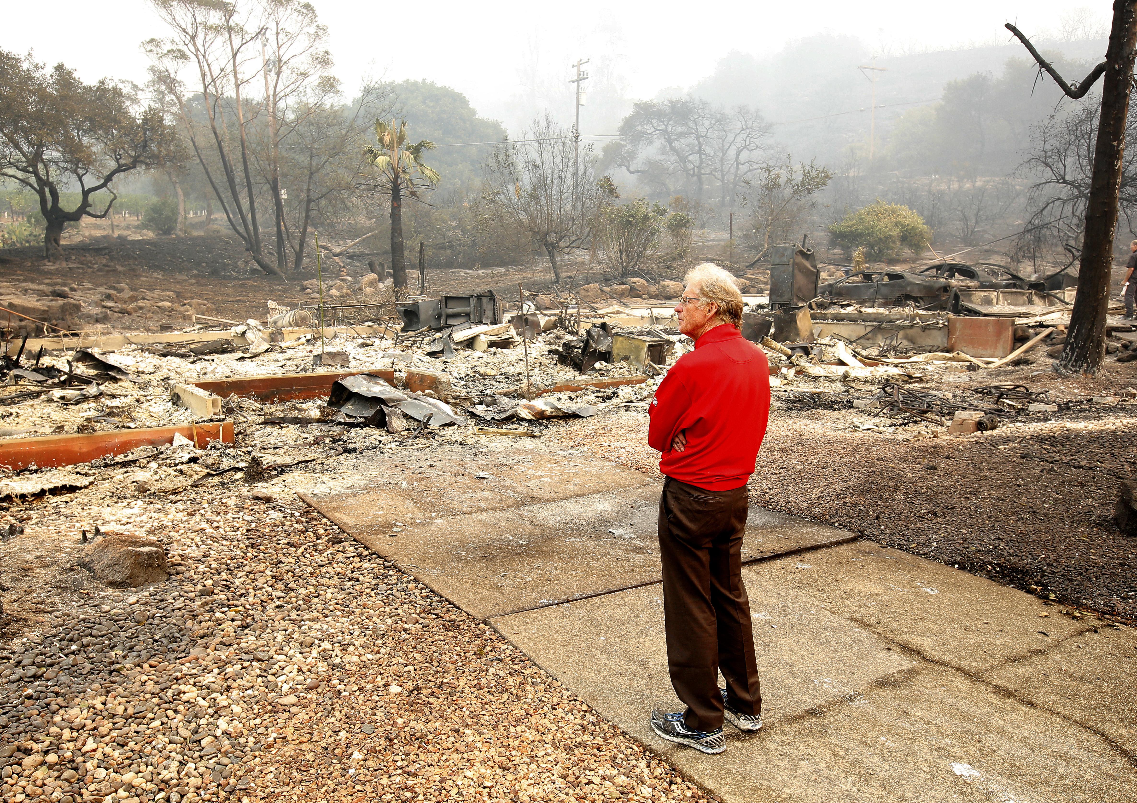 麥克.芮比(Mike Rippey)站在雙親葬身的加州住家現場,現場一片灰燼。(美聯社)