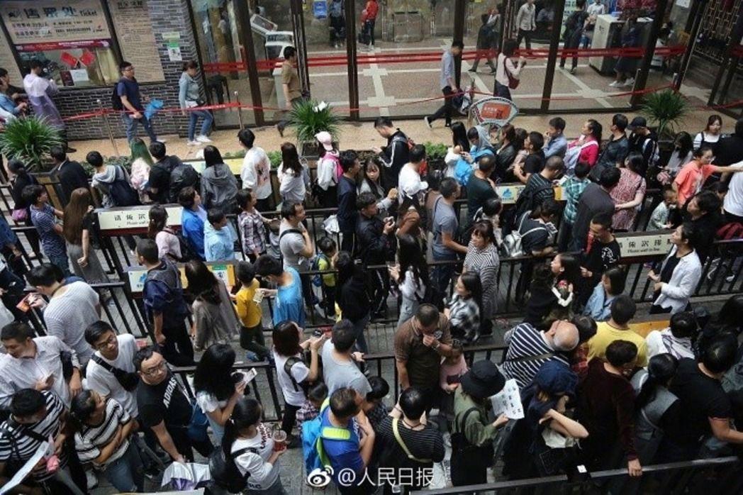眾多遊客不惜至少排隊兩小時,感受只有4分鐘的「飛躍」長江之感。(人民日報)