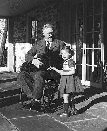 羅斯福總統甚少坐輪椅時被拍照,圖為他在Hyde Park抱著愛犬 Fala,一旁為管理員的女兒 Ruthie Bie。(Getty Images)