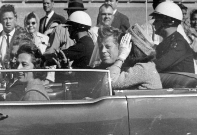 美聯社攝於1963年11月22日的這張檔案照,顯示甘迺迪總統與第一夫人賈桂琳等人乘坐專車在達拉斯向街道兩旁民眾揮手致意,隨後他即中彈遇害。國家檔案局上個月26日公布甘迺迪遇刺檔案。(美聯社)