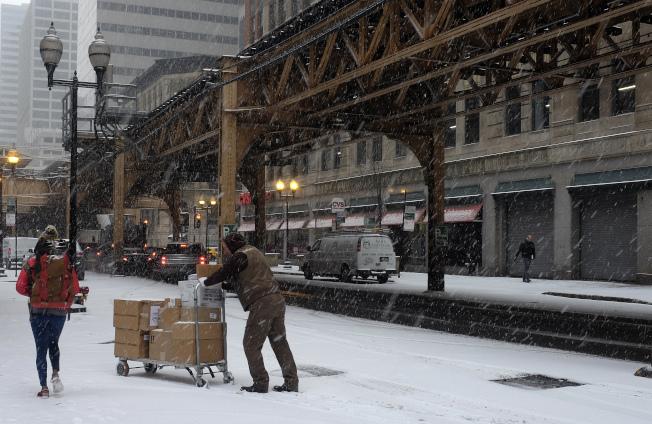 一名UPS的工作人員在芝加哥市區的雪地上,推著貨品。(美聯社)