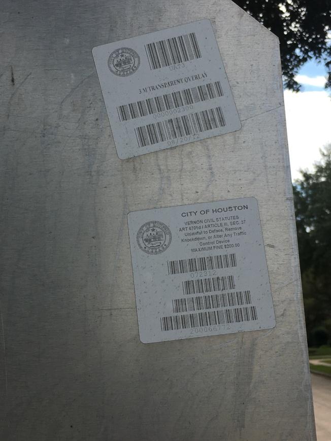 由休士頓市政府安置的標識背面有標籤及條形碼。(記者陳開/攝影)
