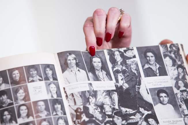 失聲指控的女子拿出高中畢業紀念冊。(路透)