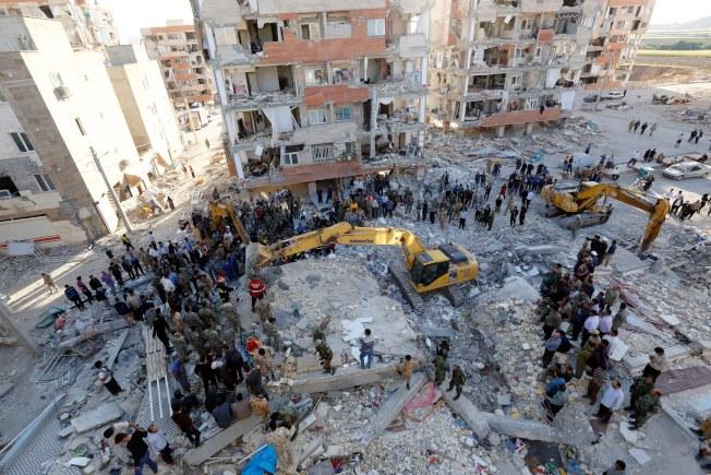 伊朗地震災情比伊拉克嚴重,圖為伊朗救災人員在災區全力搜救。(歐新社)