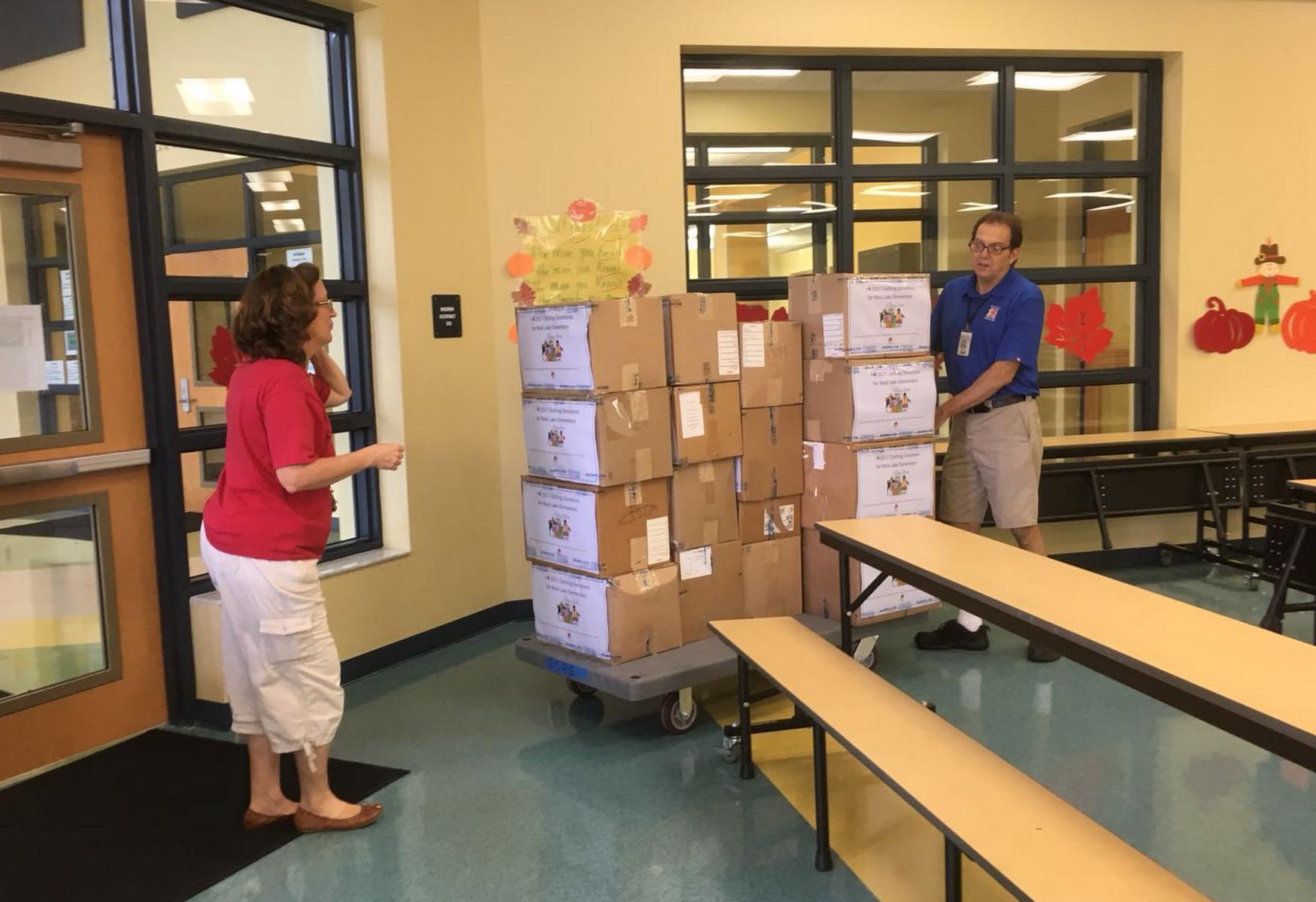 國際佛光會佛州協會奧蘭多西區分會成員送募集的衣物至岩湖小學。(鄭曼枝提供)
