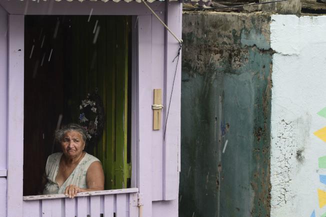 一名婦女從拉佩拉的家望向窗外。(美聯社)