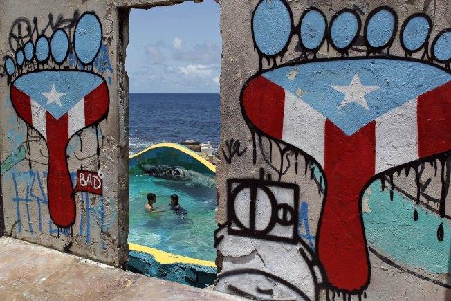 拉佩拉一隅,塗鴉牆上為波多黎各旗幟顏色,從牆望出去是碧藍的海。(美聯社)