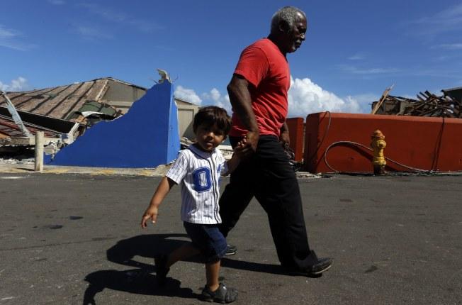 一名老翁牽著他的孫子,走在颶風過後的拉佩拉街頭。(歐新社)