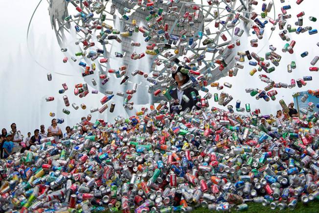 楊金池站在裝有3萬個鋁罐的鐵網下,被鐵罐緩緩滅頂。(紐文中心提供)