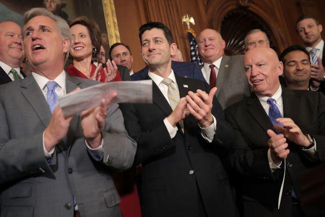 國會眾院表決通過稅改案,議長萊恩(中)、眾院多數黨領袖麥卡錫(前左)和眾院歲出入委員會主席布萊迪(前右)及其他共和黨議員鼓掌慶祝。(Getty Images)