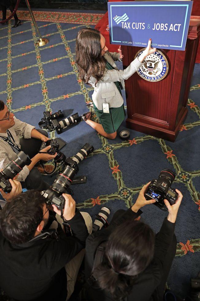 在眾院表決前,議長萊恩的助理在講台掛出減稅及工作法案的標示牌。(Getty Images)